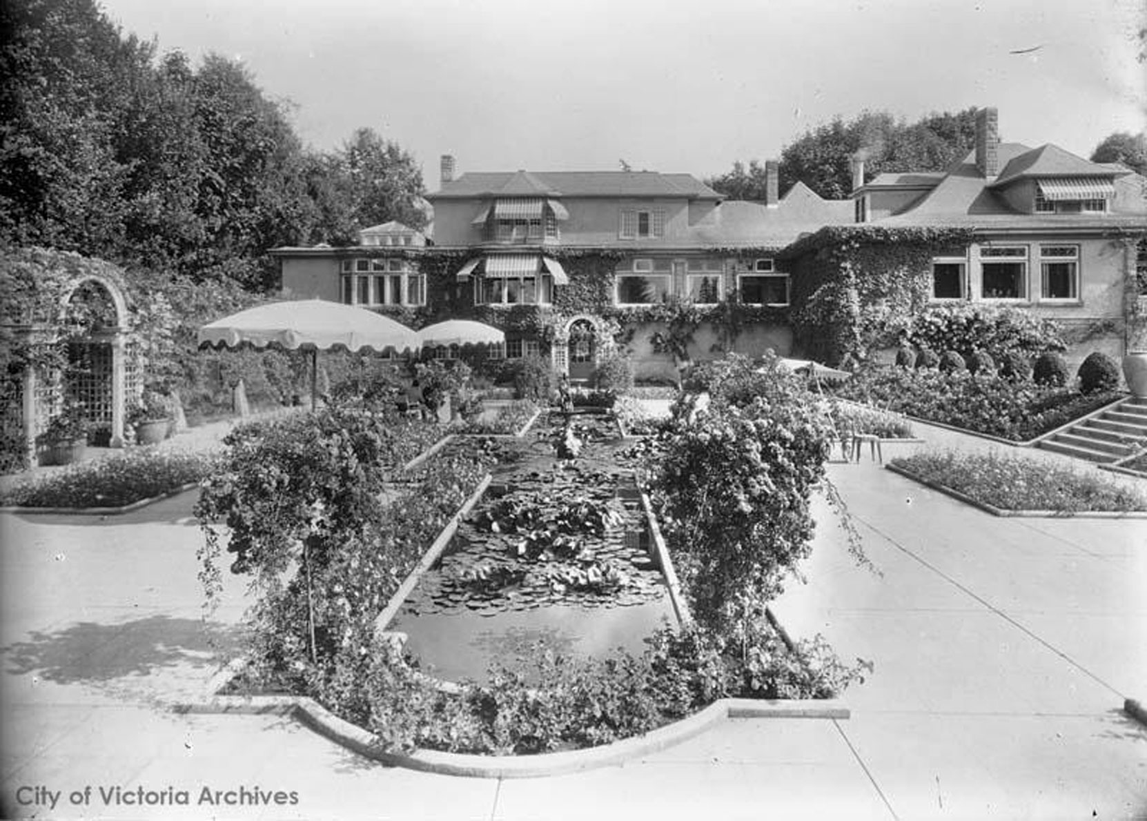 Benvenuto and the Italian Garden circa 1926-1927, prior to the addition designed by architect Samuel Maclure for the east side of Benvenuto. The Roas Arbors designed by Samuel Maclure are also visible in this photograph. (City of Victoria Archives photo M07113)