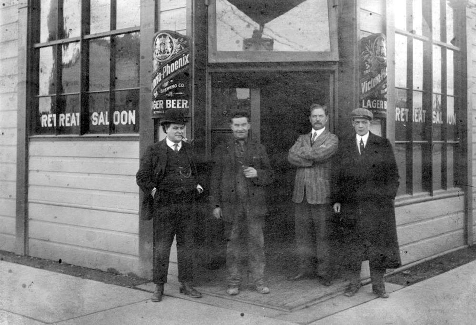 Four unidentified men outside Joseph Wrigglesworth's Retreat Saloon, on the southeast corner of Yates Street and Blanshard Street in downtown Victoria, circa 1900. Note the sign for Victoria-Phoenix Lager Beer, brewed by a Victoria based brewery. (BC Archives photo C-08971)