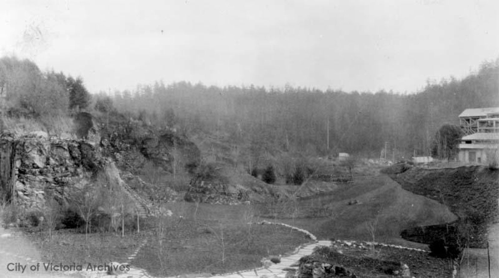 The Vancouver Portland Cement Company plant (right) above the west side of the Sunken Garden and the Mound, circa 1910. This section of the Sunken Garden was designed by Raoul Robillard. (City of Victoria Archives photo M05821)